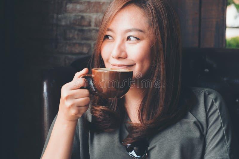 Μια όμορφη ασιατική γυναίκα που κρατά και που πίνει τον καυτό καφέ με το αίσθημα καλός στον εκλεκτής ποιότητας καφέ στοκ εικόνες