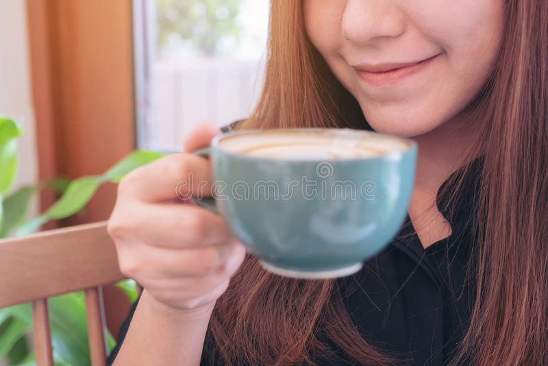 Μια όμορφη ασιατική γυναίκα που κρατά και που πίνει τον καυτό καφέ με το αίσθημα καλός στον καφέ στοκ φωτογραφία με δικαίωμα ελεύθερης χρήσης