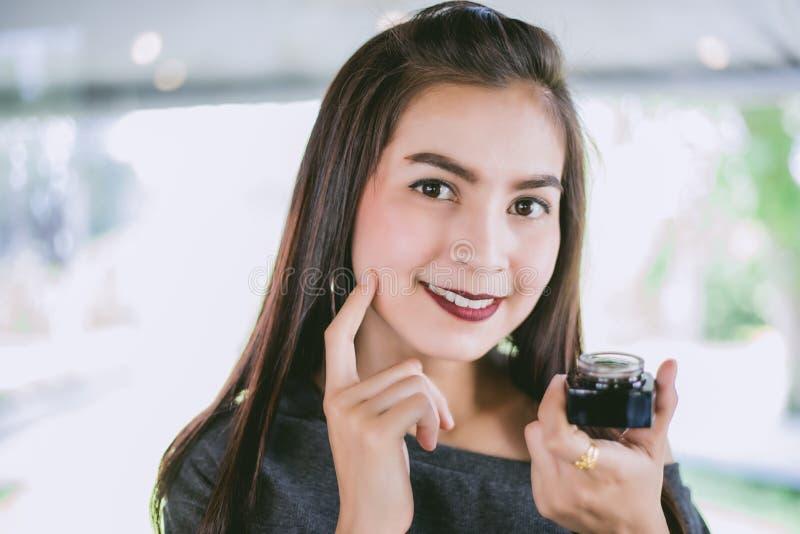 Μια όμορφη γυναίκα Ασιάτης που χρησιμοποιεί ένα προϊόν φροντίδας δέρματος, moisturizer ο στοκ φωτογραφίες