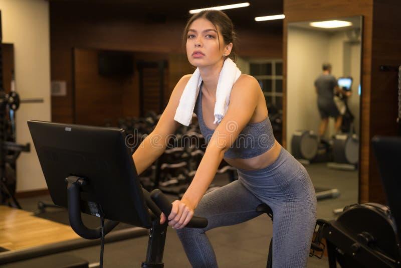 Μια όμορφη γυναίκα είναι απασχολημένη με ένα στατικό ποδήλατο στο γυμναστήριο στοκ εικόνα