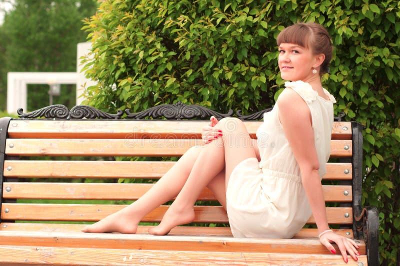 Μια όμορφη γυναίκα κάθεται σε έναν πάγκο πάρκων στοκ φωτογραφίες με δικαίωμα ελεύθερης χρήσης