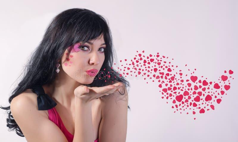 Μια όμορφη γυναίκα με μια καρδιά στο μάγουλό της φυσά σε ετοιμότητα της στοκ φωτογραφίες με δικαίωμα ελεύθερης χρήσης