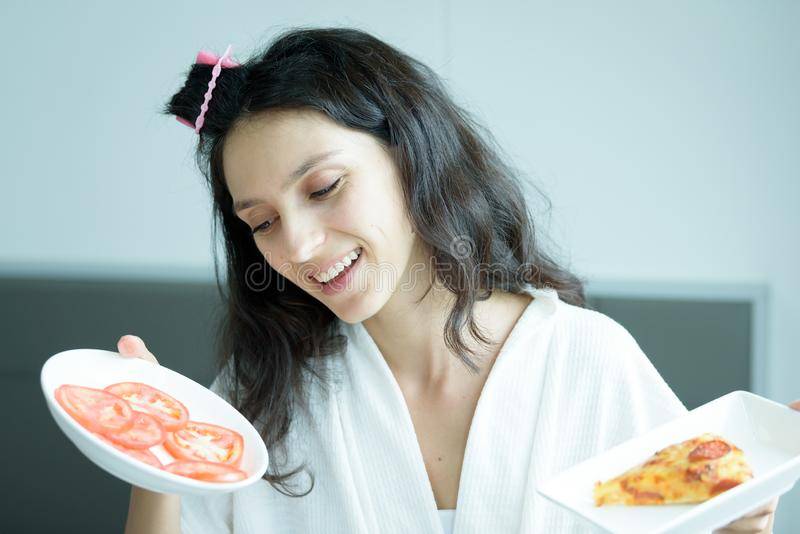 Μια όμορφη γυναίκα με πετσέτα και μια λευκή ρόμπα πρέπει να φάει μια πίτσα και να κόψει ντομάτα με χαρά και ηρεμία στο κρεβάτι στοκ εικόνες
