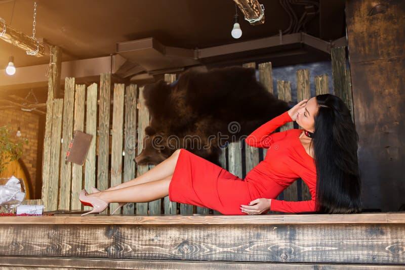 Μια όμορφη γυναίκα σε ένα κόκκινο φόρεμα βρίσκεται στοκ φωτογραφία με δικαίωμα ελεύθερης χρήσης