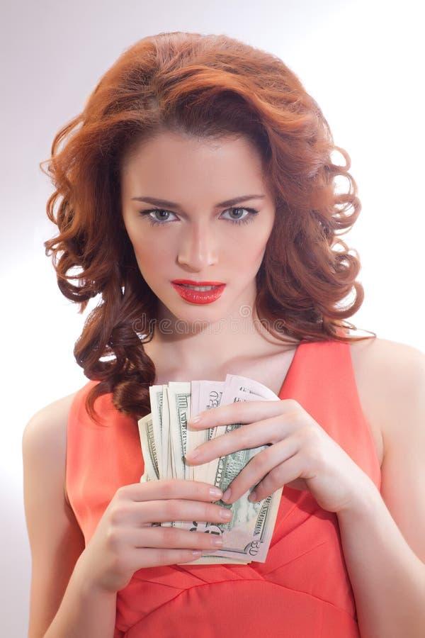 Μια όμορφη γυναίκα σε ένα ρόδινο φόρεμα με τα τραπεζογραμμάτια δολαρίων στα χέρια στοκ φωτογραφία με δικαίωμα ελεύθερης χρήσης