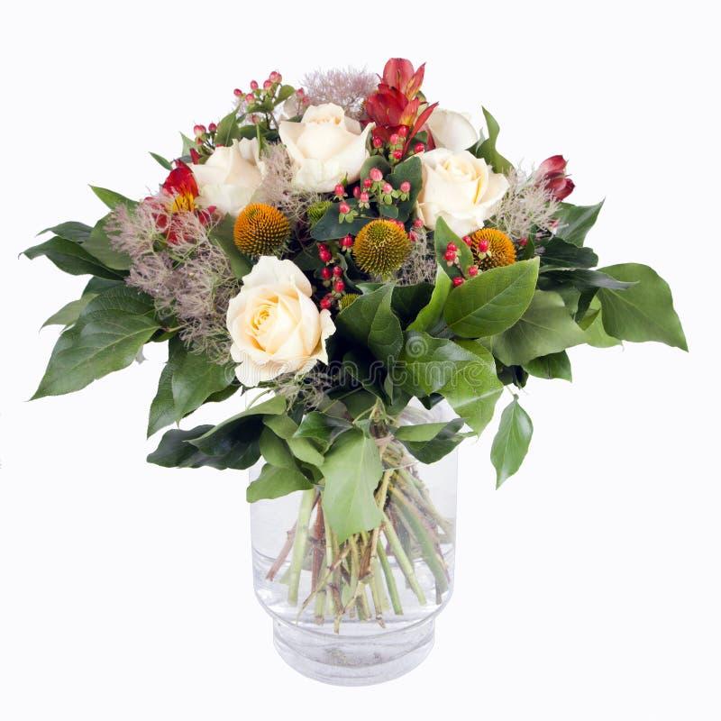 Μια όμορφη δέσμη των άσπρων τριαντάφυλλων και των κόκκινων ανθών σε ένα βάζο γυαλιού στοκ εικόνα