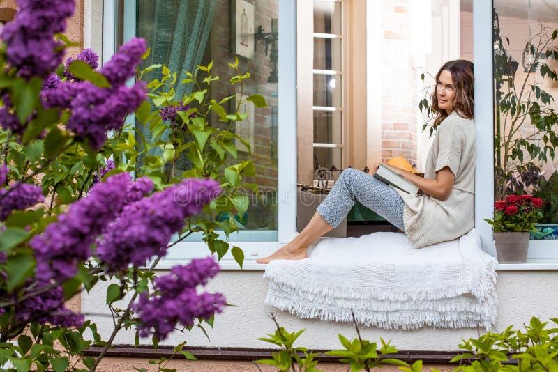 Μια όμορφη μέσης ηλικίας γυναίκα με ένα βιβλίο στοκ εικόνα
