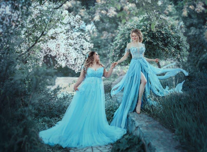 Μια όμορφη μεγάλη γυναίκα κρατά ένα εύθραυστο ξανθό κορίτσι στο χέρι της Δύο πριγκήπισσες στα πολυτελή μπλε φορέματα ενάντια στοκ φωτογραφίες