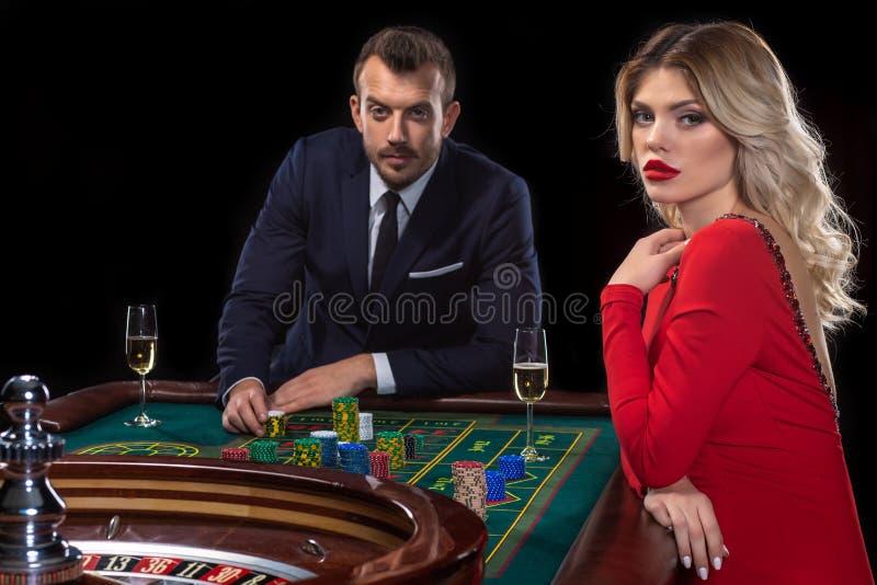 Μια όμορφη νέα γυναίκα και ένας άνδρας κάθονται σε έναν πίνακα ρουλετών casino στοκ εικόνα