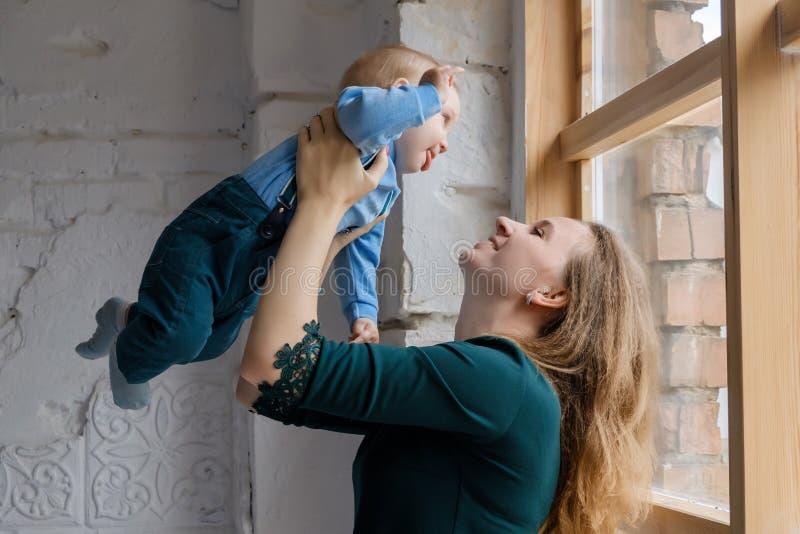 Μια όμορφη νέα μητέρα στέκεται κοντά σε ένα μεγάλο παράθυρο και κρατά το γιο της στα όπλα της στοκ εικόνες