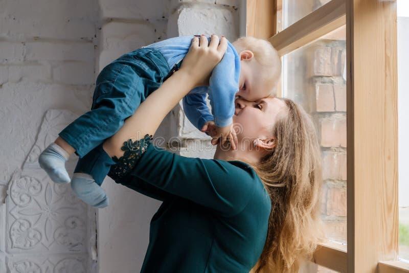 Μια όμορφη νέα μητέρα στέκεται κοντά σε ένα μεγάλο παράθυρο και κρατά το γιο της στα όπλα της στοκ εικόνα