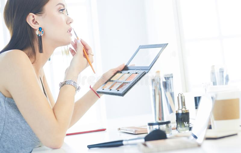 Μια όμορφη νέα συνεδρίαση γυναικών σε έναν πίνακα makeup και να κάνει το makeup της στοκ εικόνα
