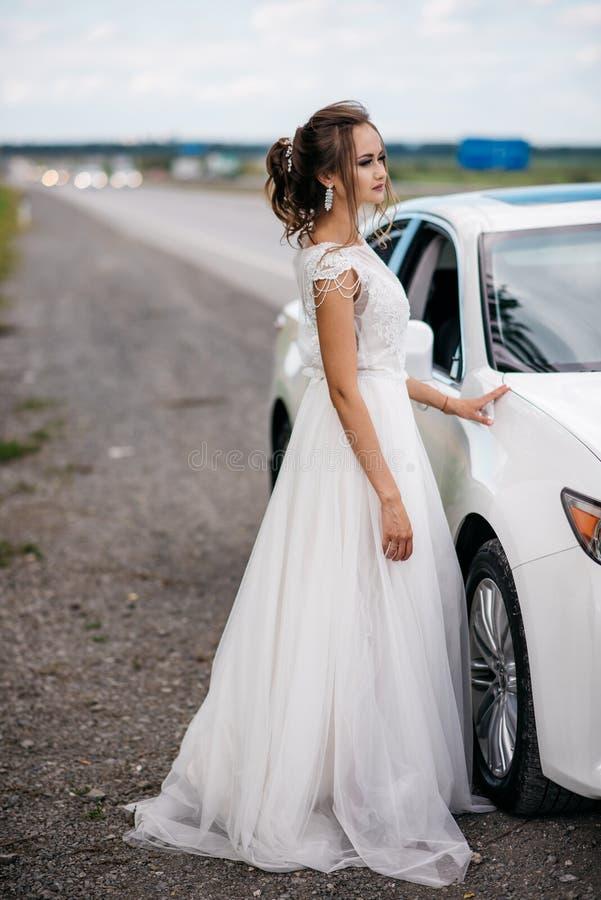 Μια όμορφη νύφη σε ένα γαμήλιο φόρεμα στέκεται δίπλα σε ένα άσπρο αυτοκίνητο από το δρόμο στοκ εικόνα