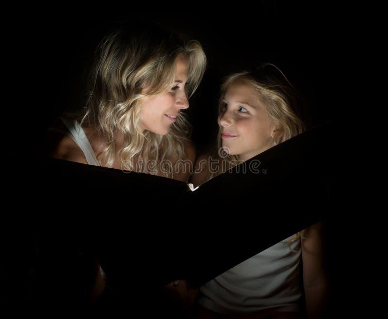 Μια όμορφη ξανθή μητέρα και το παιδί της μαζί με ένα μεγάλο βιβλίο στο σκοτάδι στοκ εικόνα