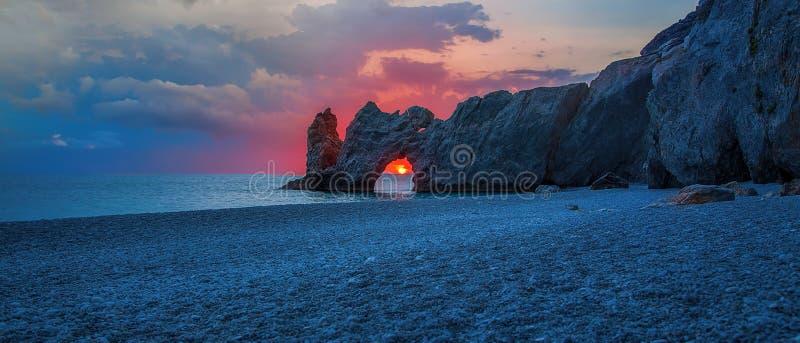 Μια όμορφη παραλία στην ανατολή με τον ήλιο στην τρύπα των βράχων στοκ φωτογραφία