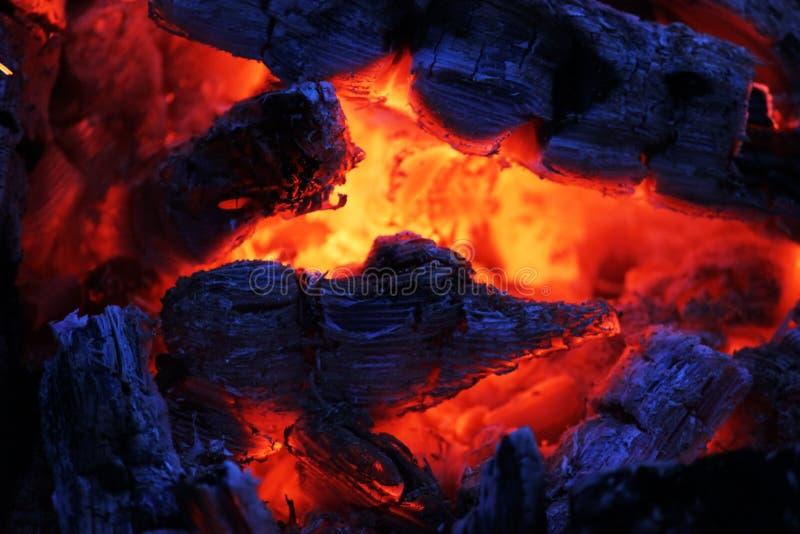 Μια όμορφη πυρκαγιά βραδιού που λειώνει μακριά με τους κόκκινους άνθρακες στοκ εικόνες