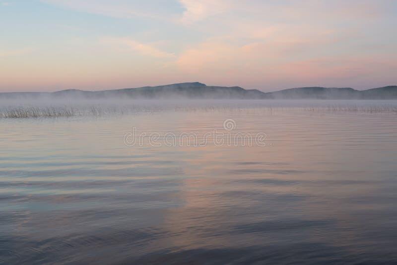 Μια όμορφη ρόδινη αυγή απεικονίζεται στη μεγάλη λίμνη στοκ εικόνα