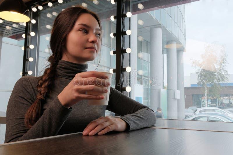 Μια όμορφη συνεδρίαση νέων κοριτσιών μόνο σε μια καφετερία Το κορίτσι πίνει το καυτό τσάι και basks μια βροχερή ημέρα άνοιξη στοκ εικόνες