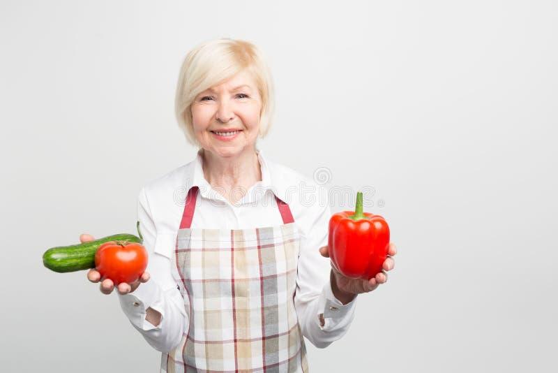 Μια όμορφη ώριμη γυναίκα που κρατά ένα κόκκινο πιπέρι στο αριστερό χέρι και ντομάτα και αγγούρι στο δεξή Συμπαθεί στοκ εικόνα με δικαίωμα ελεύθερης χρήσης