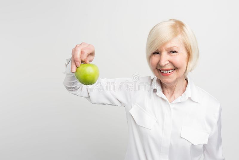 Μια όμορφη ώριμη γυναίκα που κρατά ένα πράσινο μήλο σε δεξή Επιθυμεί να φάει τα φρούτα Αυτό είναι η επιλογή της E στοκ φωτογραφία με δικαίωμα ελεύθερης χρήσης