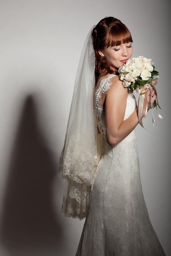 Μια beautyful νύφη εξετάζει κάτω την ανθοδέσμη της από τα τριαντάφυλλα. στοκ εικόνες