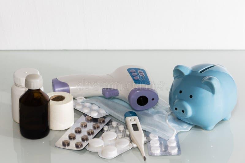 Μια piggy τράπεζα κάθεται πάνω από τα χάπια για να πληρώσει για τις αυξανόμενες τιμές φαρμάκων η υγεία προσοχής όπλων απομόνωσε τ στοκ φωτογραφίες
