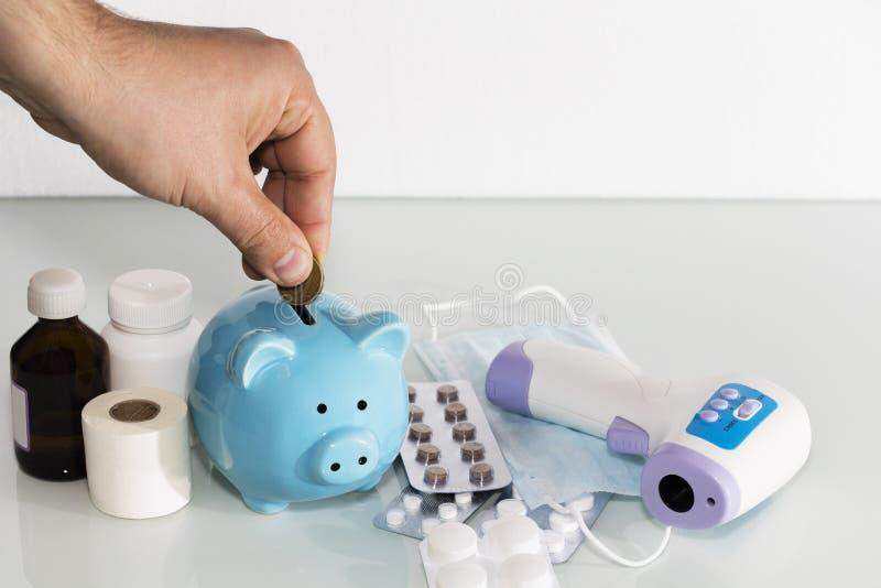 Μια piggy τράπεζα κάθεται πάνω από τα χάπια για να πληρώσει για τις αυξανόμενες τιμές φαρμάκων η υγεία προσοχής όπλων απομόνωσε τ στοκ φωτογραφία με δικαίωμα ελεύθερης χρήσης