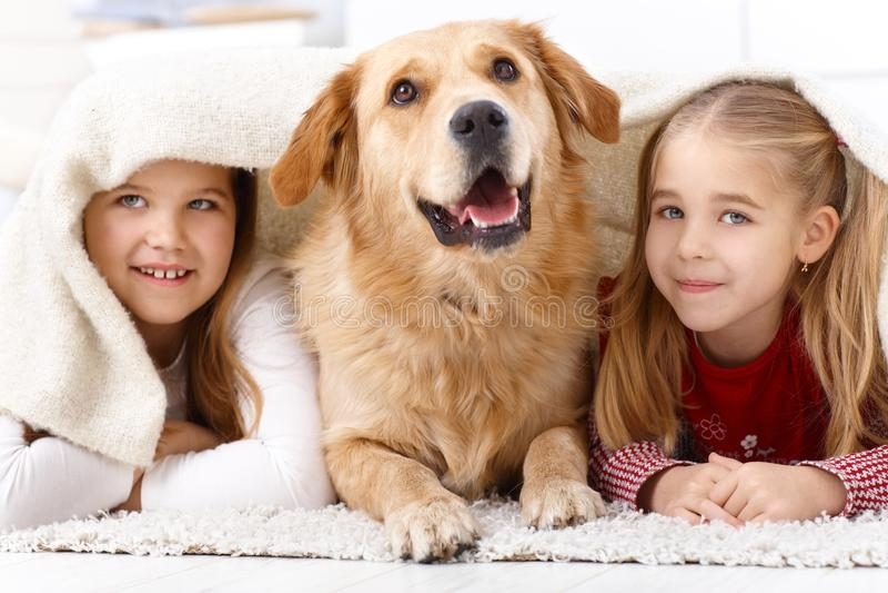 Μικρά αδελφές και σκυλί κατοικίδιων ζώων που χαμογελά στο σπίτι στοκ εικόνες με δικαίωμα ελεύθερης χρήσης