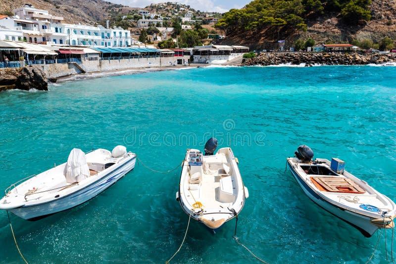 Μικρά δεμένα αλιευτικά σκάφη στην μπλε λιμνοθάλασσα του νησιού της Κρήτης στοκ φωτογραφία