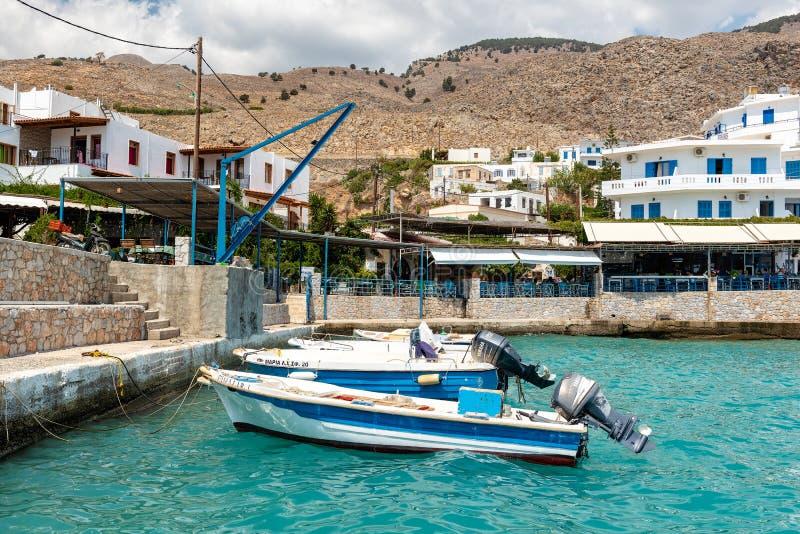 Μικρά δεμένα αλιευτικά σκάφη στην μπλε λιμνοθάλασσα του νησιού της Κρήτης στοκ εικόνες