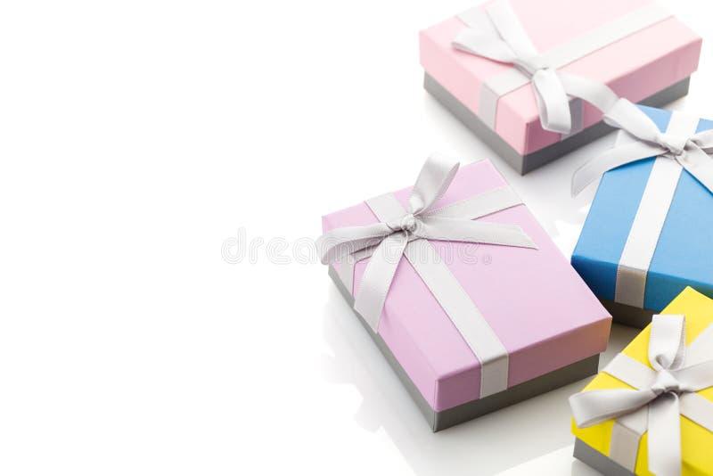 Μικρά ζωηρόχρωμα κιβώτια δώρων με τα τόξα κορδελλών στο άσπρο υπόβαθρο στοκ εικόνες