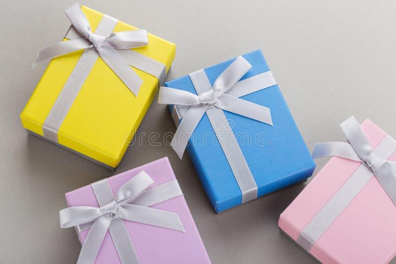 Μικρά ζωηρόχρωμα κιβώτια δώρων με τα τόξα κορδελλών στο γκρίζο υπόβαθρο στοκ εικόνες με δικαίωμα ελεύθερης χρήσης