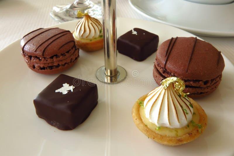 Μικρά κέικ Petits fours στο άσπρο πιάτο στοκ εικόνες