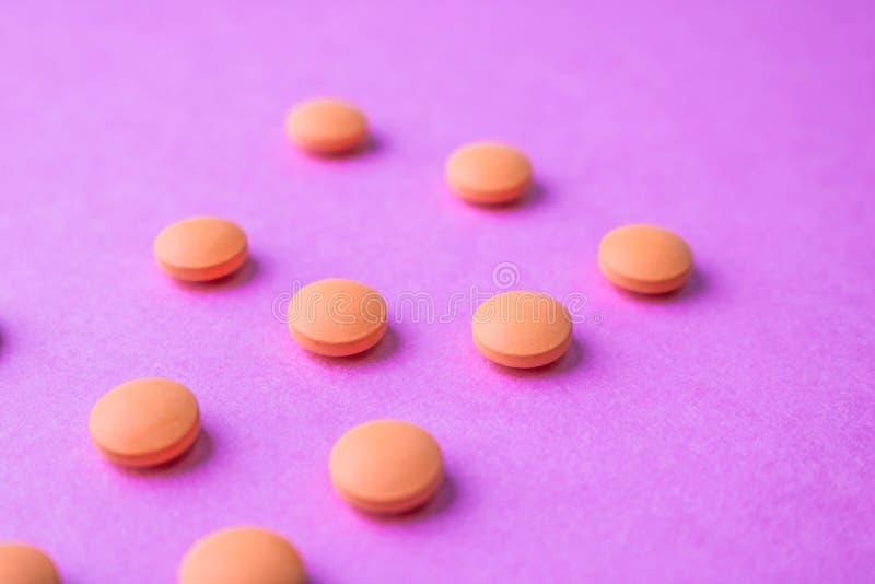 Μικρά κίτρινα πορτοκαλιά όμορφα ιατρικά pharmaceptic στρογγυλά χάπια, βιταμίνες, φάρμακα, αντιβιοτικά σε ένα ρόδινο πορφυρό υπόβα στοκ εικόνες με δικαίωμα ελεύθερης χρήσης