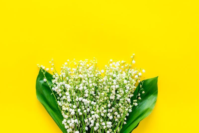 Μικρά και ευώδη λουλούδια άνοιξη Το Bouqet του κρίνου της κοιλάδας ανθίζει στο κίτρινο διάστημα αντιγράφων άποψης υποβάθρου τοπ στοκ φωτογραφία