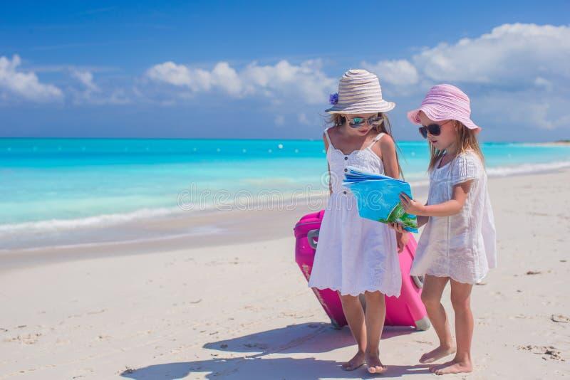 Μικρά καλά κορίτσια με τη μεγάλη βαλίτσα και έναν χάρτη στην τροπική παραλία στοκ εικόνες