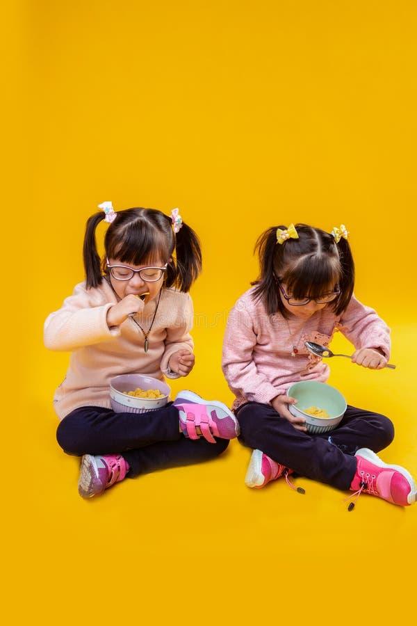Μικρά κορίτσια με τη διανοητηκή διαταραχή που τρώνε τα δημητριακά με το γάλα στοκ φωτογραφία με δικαίωμα ελεύθερης χρήσης