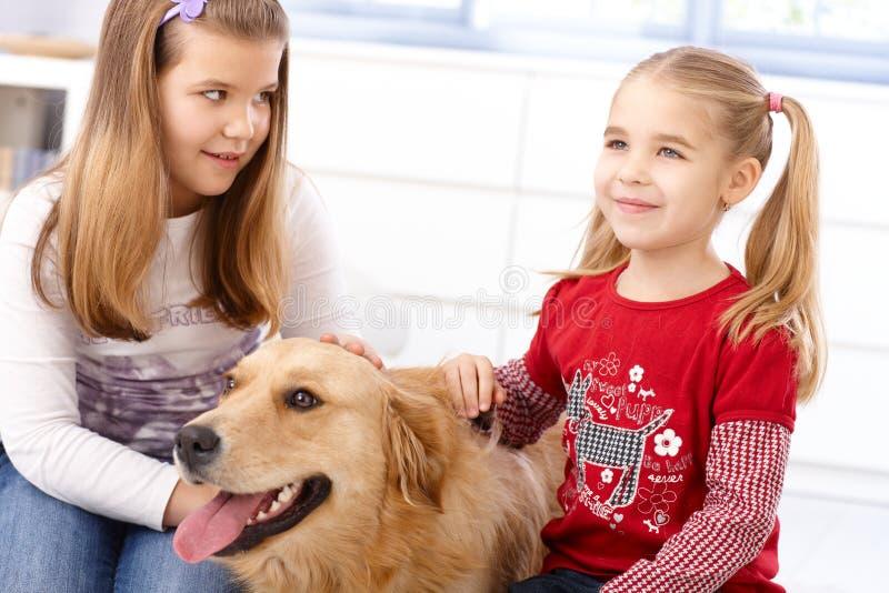 Μικρά κορίτσια με το σκυλί στο σπίτι στοκ φωτογραφία με δικαίωμα ελεύθερης χρήσης