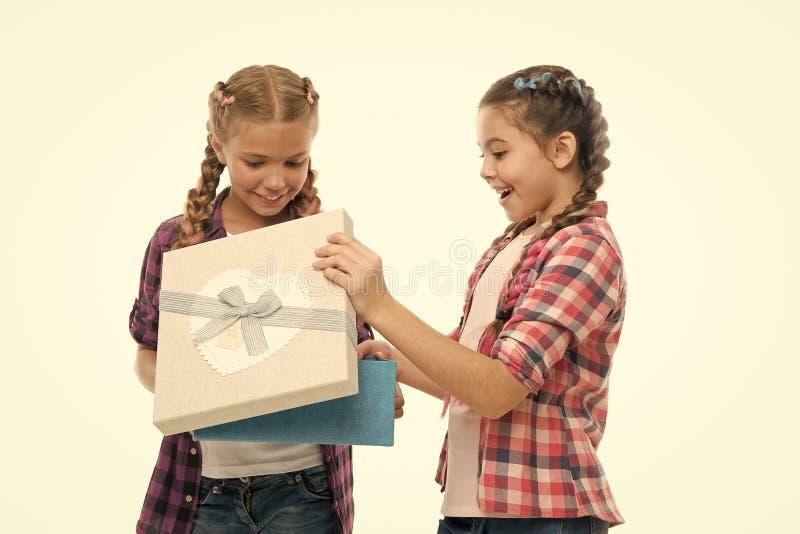 Μικρά κορίτσια παιδιών με το κιβώτιο δώρων λαβής πλεξουδών hairstyle Παιδιά που διεγείρονται για να ανοίξει το δώρο Μικρές χαριτω στοκ εικόνες