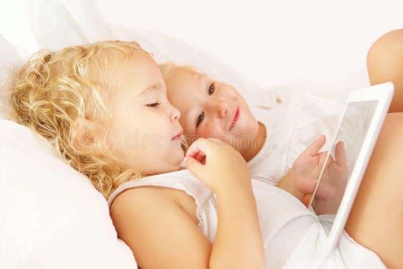 Μικρά κορίτσια που εξετάζουν την ψηφιακή ταμπλέτα στο κρεβάτι στοκ φωτογραφίες