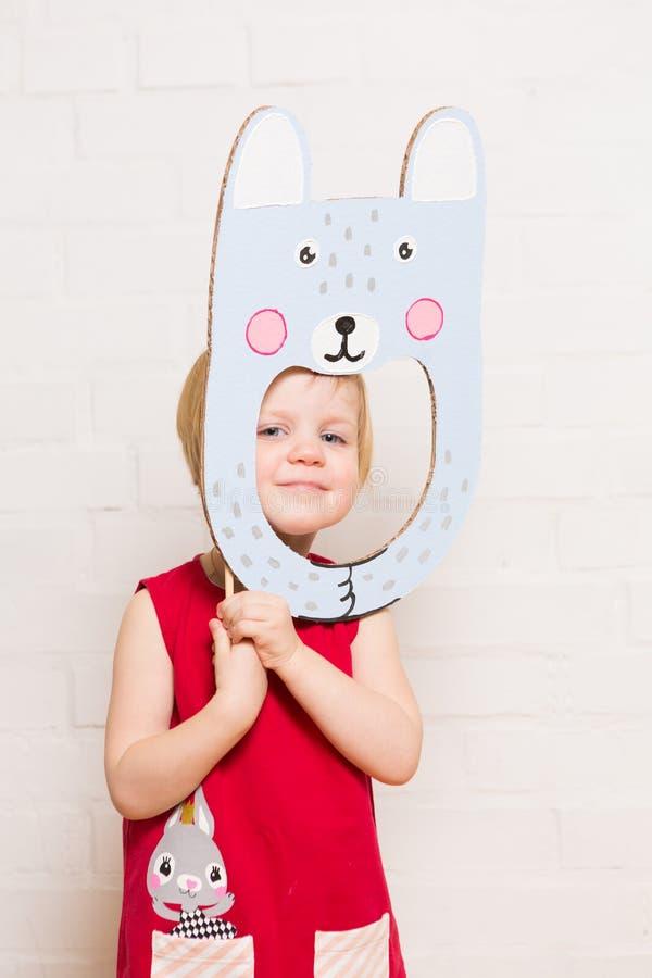 Μικρά κορίτσια που κρατούν τη μάσκα κουνελιών στο άσπρο υπόβαθρο στοκ εικόνες