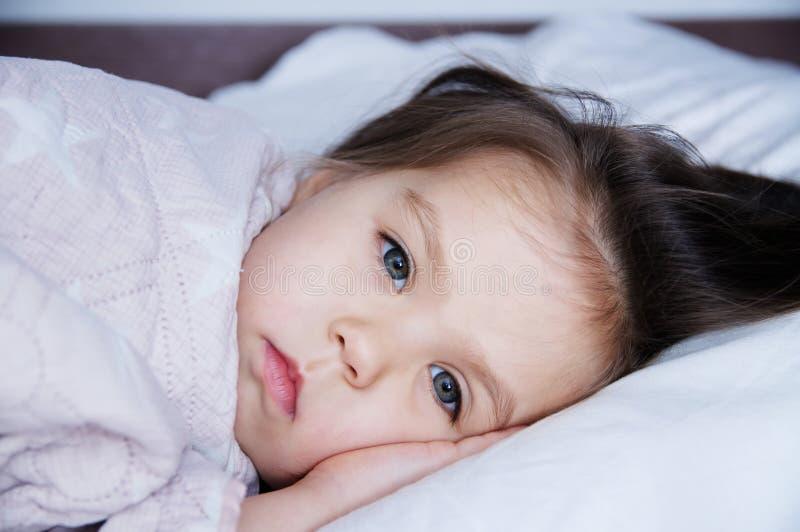 Μικρά κορίτσια που πηγαίνουν στον ύπνο που βρίσκεται στο κρεβάτι πρόγραμμα ύπνου στον εσωτερικό τρόπο ζωής χαριτωμένο πορτρέτο πα στοκ εικόνα με δικαίωμα ελεύθερης χρήσης