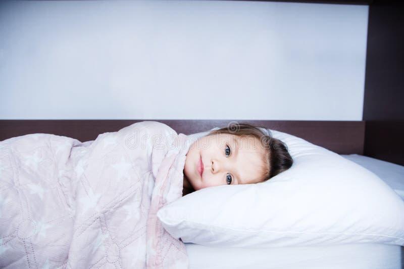 Μικρά κορίτσια που πηγαίνουν στον ύπνο που βρίσκεται στο κρεβάτι πρόγραμμα ύπνου στον εσωτερικό τρόπο ζωής χαριτωμένο πορτρέτο πα στοκ φωτογραφία με δικαίωμα ελεύθερης χρήσης