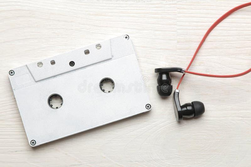 Μικρά κόκκινος-μαύρα ακουστικά και ακουστική κασέτα σε ένα άσπρο ξύλινο υπόβαθρο r στοκ φωτογραφία με δικαίωμα ελεύθερης χρήσης