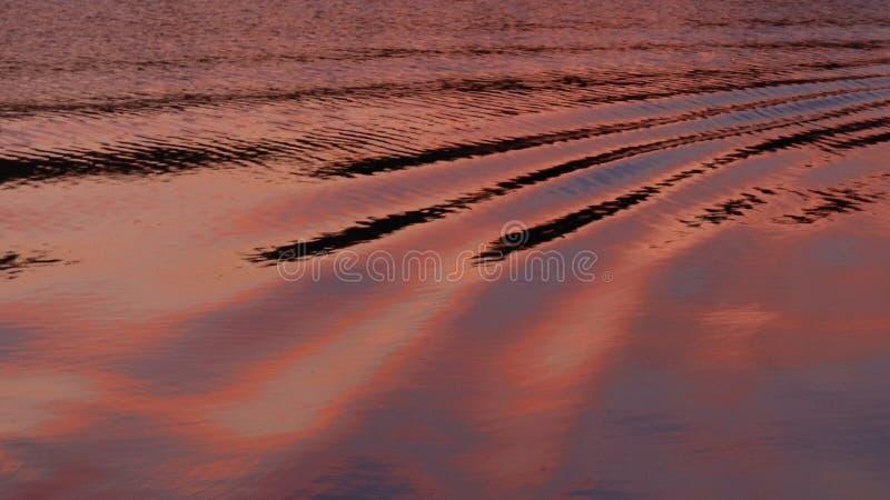 Μικρά κύματα στο νερό που απεικονίζουν τα χρώματα ηλιοβασιλέματος στοκ εικόνες με δικαίωμα ελεύθερης χρήσης