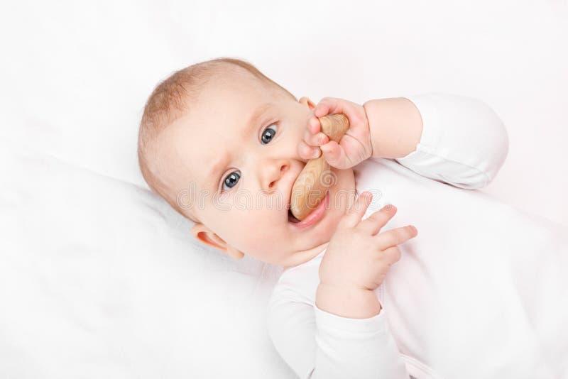 Μικρά μωρουδίστικα μασάει ξύλινα θηράματα στοκ εικόνες