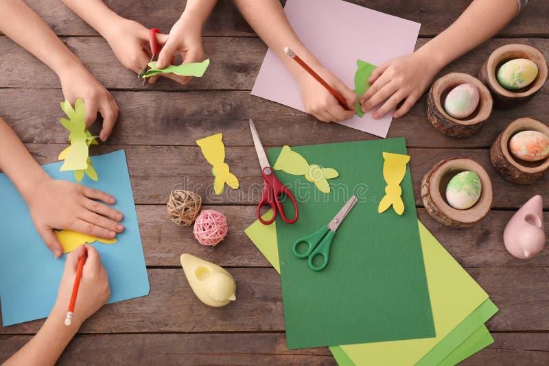 Μικρά παιδιά που κάνουν τις διακοσμήσεις Πάσχας στον πίνακα στοκ φωτογραφία με δικαίωμα ελεύθερης χρήσης
