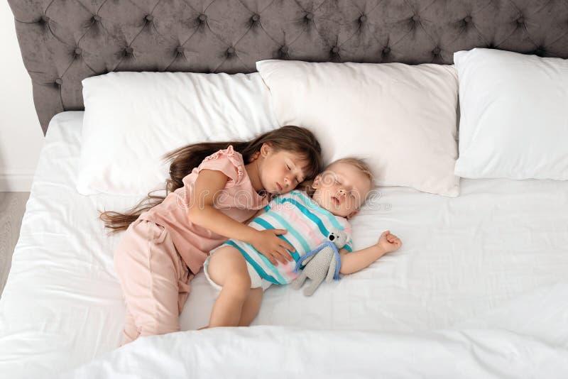 Μικρά παιδιά που κοιμούνται στο κρεβάτι στοκ φωτογραφία