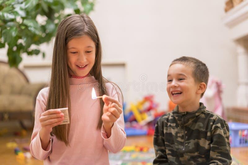 Μικρά παιδιά που παίζουν με τη φωτιά στο σπίτι Παιδικά παιχνίδια με τις αντιστοιχίες στο πρώτο πλάνο μια καίγοντας αντιστοιχία, έ στοκ εικόνα
