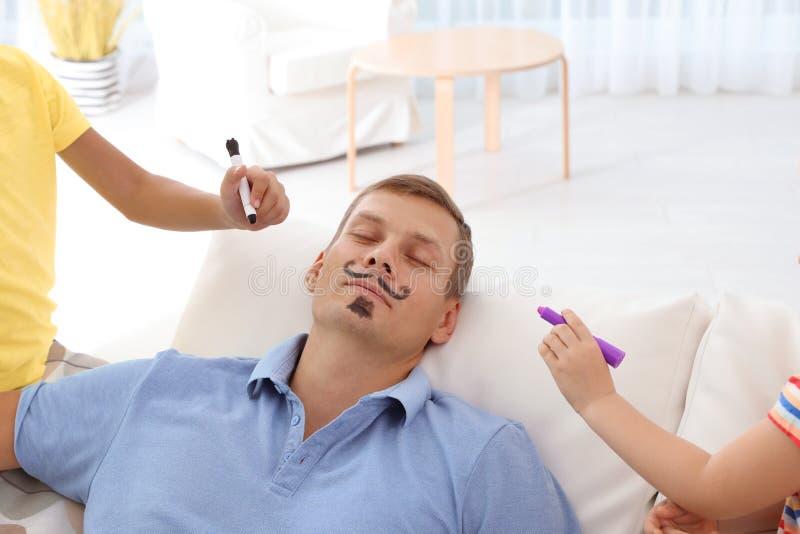 Μικρά παιδιά που χρωματίζουν το πρόσωπο του πατέρα τους ενώ αυτός ύπνος στον καναπέ στο σπίτι στοκ φωτογραφία